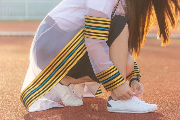 Donna che lega il laccio delle scarpe da ginnastica alla moda dei pantaloni a vita bassa prima dell'inizio sulla pista corrente all'obiettivo Foto Premium