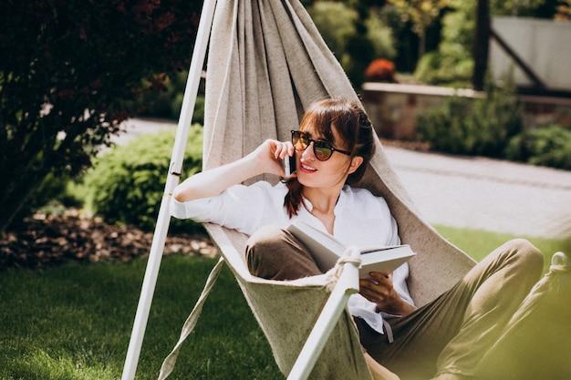 Donna che legge un libro nel giardino vicino alla casa Foto Gratuite