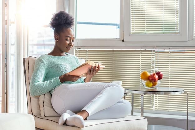 Donna che legge un libro su una sedia Foto Premium