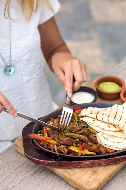 Donna che mangia agnello in padella con peperoni colorati, servito con focaccia Foto Gratuite