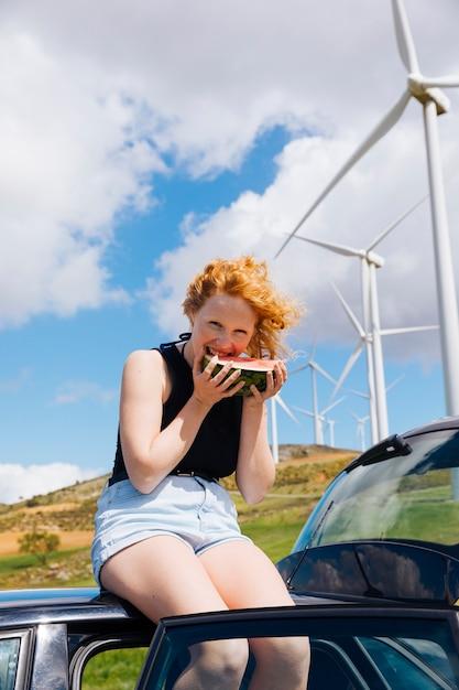 Donna che mangia anguria sul tetto dell'auto Foto Gratuite