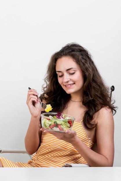 Donna che mangia un'insalata di lattuga Foto Gratuite