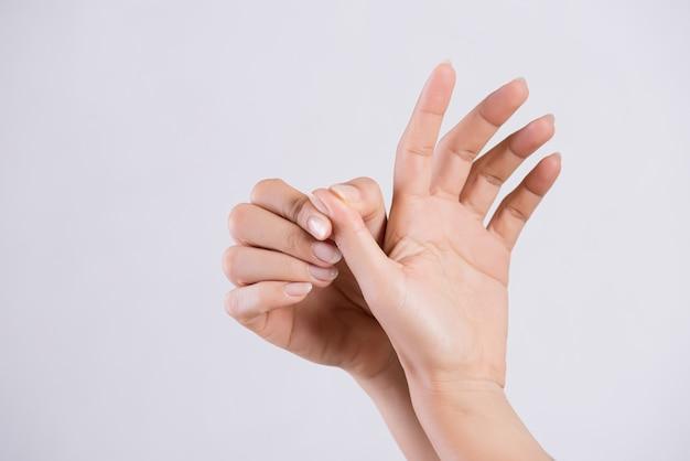 Donna che massaggia il suo dito doloroso del pollice, concetto di sanità. Foto Premium
