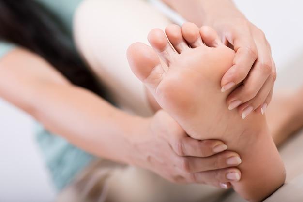 Donna che massaggia il suo piede doloroso, concetto di sanità. Foto Premium