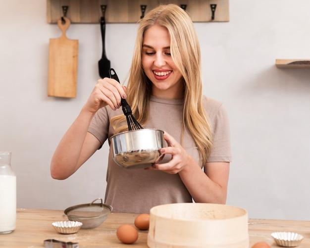 Donna che mescola le uova in una ciotola metallica Foto Gratuite