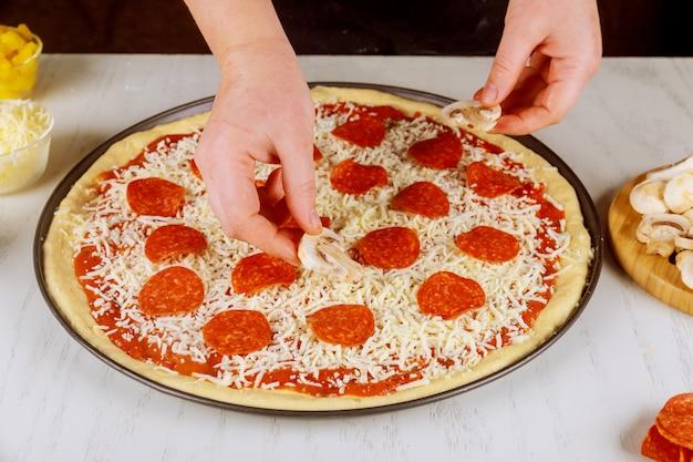 Donna che mette i funghi su pizza cruda cruda. Foto Premium