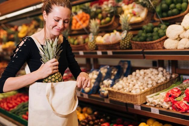 Donna che mette un ananas in una borsa Foto Gratuite