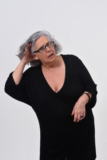 Donna che mette una mano sul suo orecchio perché non può sentire su fondo bianco Foto Premium