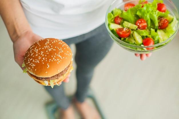 Donna che misura il peso corporeo sulla bilancia tenendo hamburger e insalata, i dolci sono cibo spazzatura malsano, dieta, alimentazione sana, stile di vita, perdita di peso, obesità, vista dall'alto Foto Premium