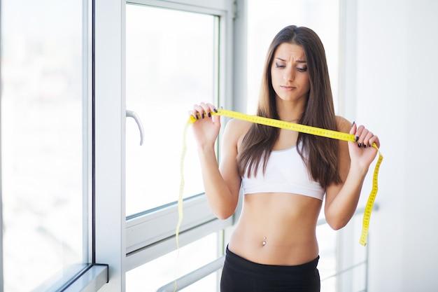 Donna che misura la vita dopo l'allenamento. mani che misurano la vita con un nastro. donna magra e in buona salute Foto Premium