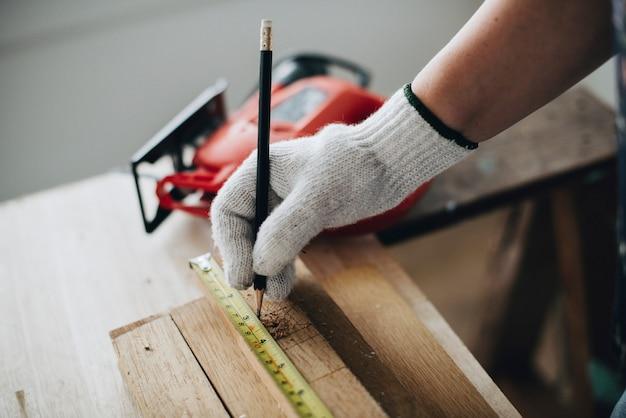 Donna che misura una tavola di legno Foto Gratuite