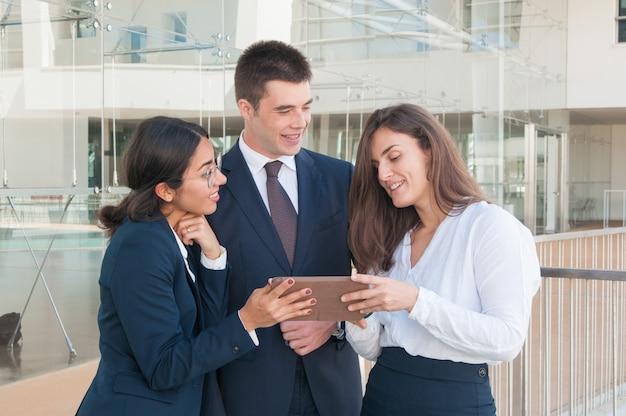 Donna che mostra i dati sul tablet, colleghi che sembrano coinvolti Foto Gratuite
