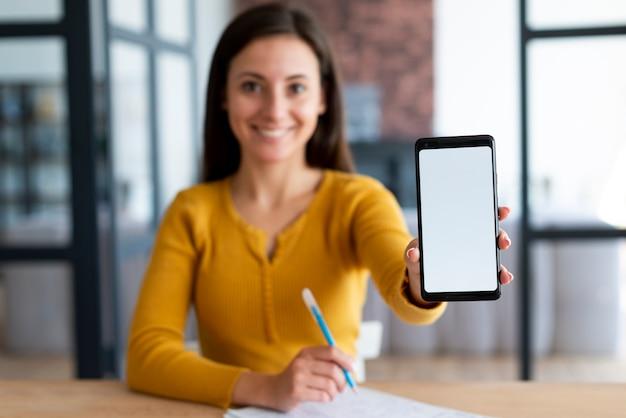 Donna che mostra il suo schermo del telefono Foto Gratuite