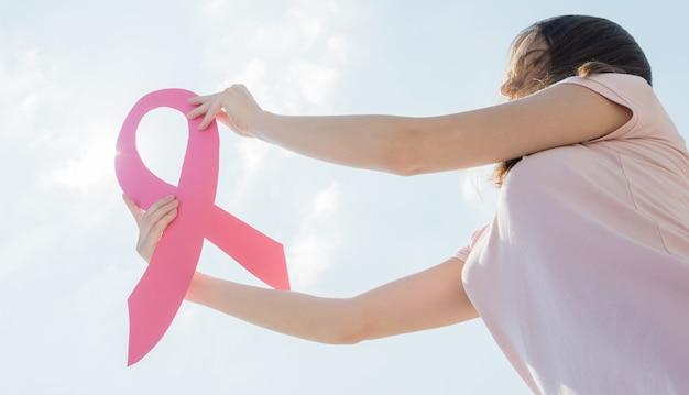 Donna che mostra nastro rosa per sostenere il cancro al seno. Foto Premium