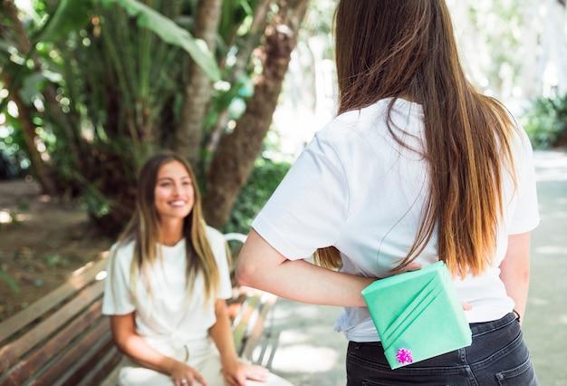 Donna che nasconde il regalo per l'amico alle sue spalle Foto Gratuite