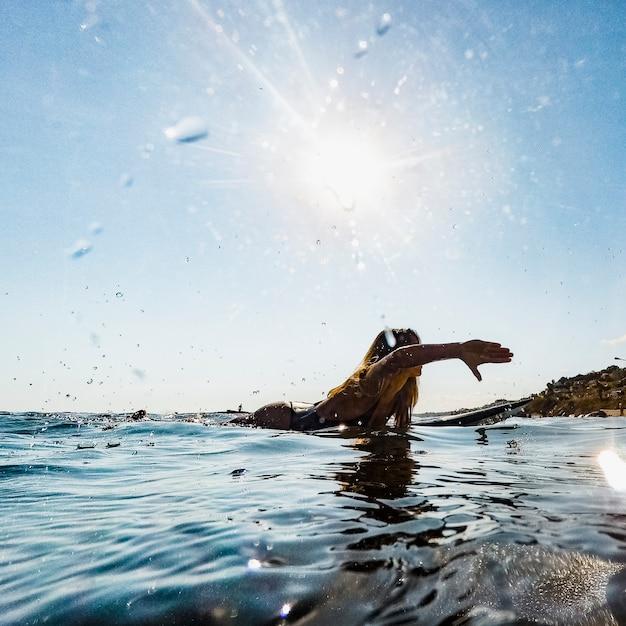 Donna che nuota sulla tavola da surf in acqua Foto Gratuite