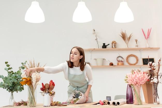 Donna che organizza i mazzi di fiori nel suo negozio Foto Gratuite