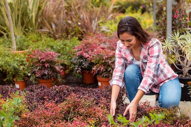 Donna che organizza le piante in giardino Foto Gratuite