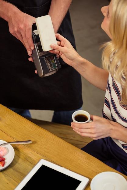 Donna che paga con pagamento mobile Foto Premium