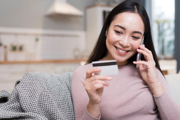 Donna che parla al telefono mentre ostacola la carta di credito Foto Gratuite