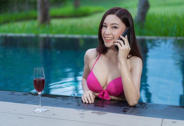 Donna che parla su un telefono cellulare in piscina Foto Premium