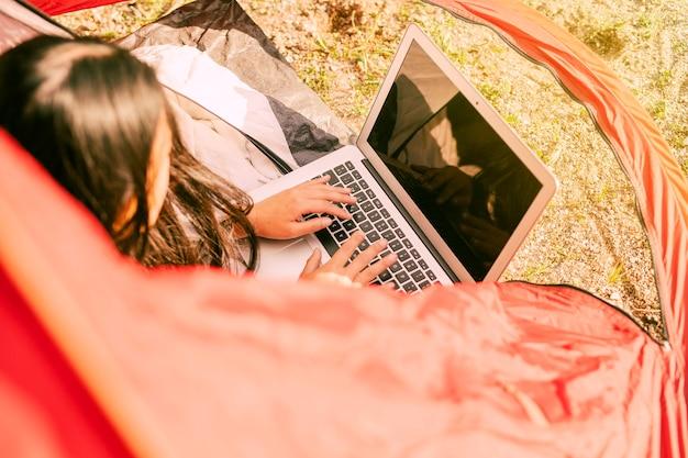 Donna che per mezzo del computer portatile mentre riposando nel campeggio Foto Gratuite