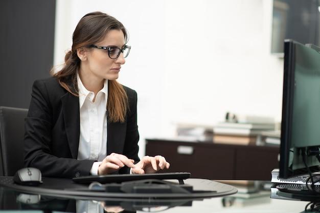 Donna che per mezzo del suo computer sul lavoro Foto Premium