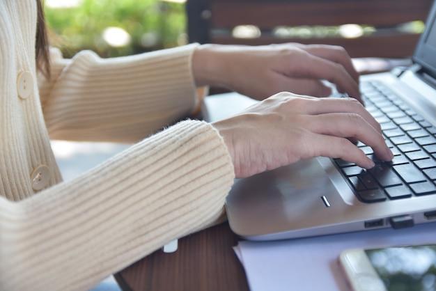 Donna che per mezzo del taccuino del computer Foto Premium