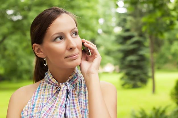 Donna che per mezzo del telefono cellulare all'aperto Foto Premium