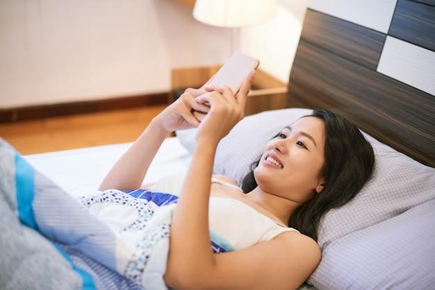 Donna che per mezzo del telefono mentre trovandosi a letto Foto Gratuite