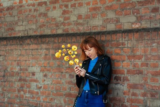 Donna che per mezzo dello smartphone che invia gli emoji. Foto Premium