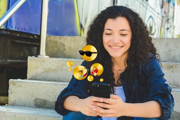 Donna che per mezzo dello smartphone che invia gli emoji Foto Premium