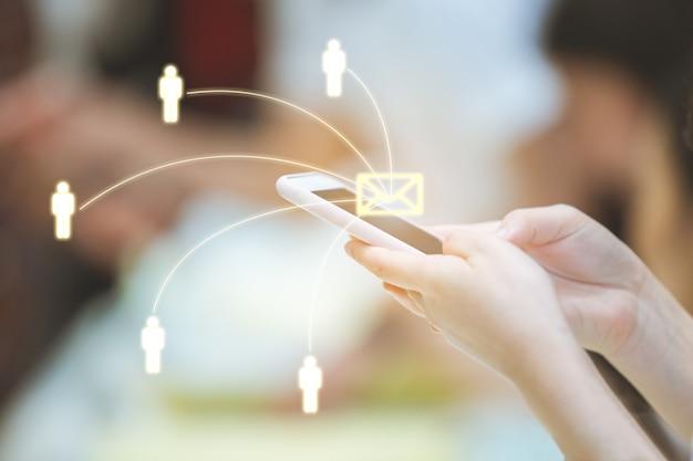 Donna che per mezzo dello smartphone che invia messaggio dall'e-mail ad altre persone con la rete. Foto Premium