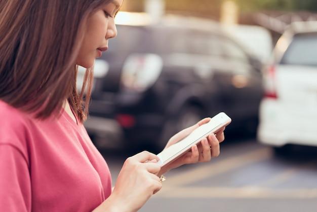 Donna che per mezzo dello smartphone per l'applicazione sulla priorità bassa della sfuocatura dell'automobile. Foto Premium