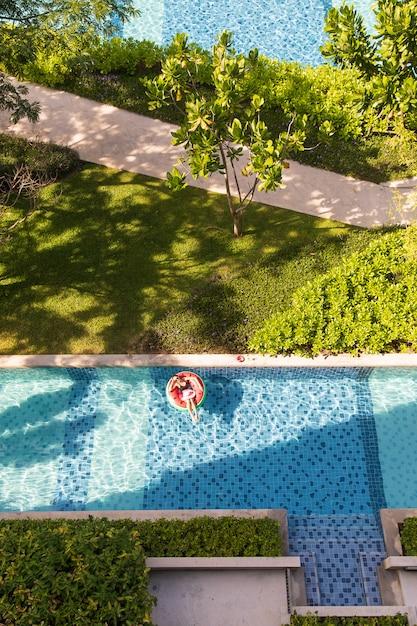 Donna che pone sul pallone in piscina Foto Premium