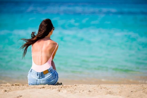 Donna che pone sulla spiaggia godendo le vacanze estive guardando il mare Foto Premium