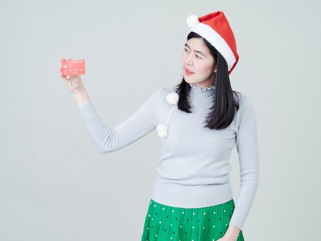 Donna che porta a disposizione il cappello di santa che mostra la compera delle carte di credito Foto Premium