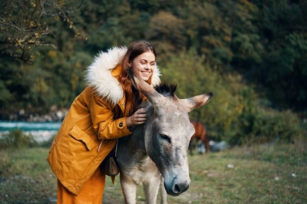 Donna che posa con un asino sulla natura nelle montagne Foto Premium