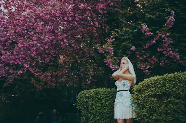 Donna che posa per una foto in un giardino Foto Premium