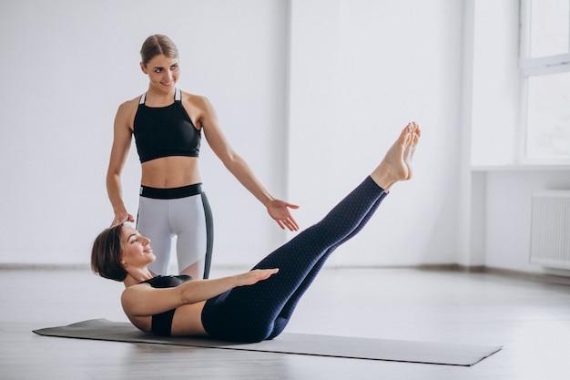 Donna che pratica yoga in palestra con l'allenatore Foto Gratuite