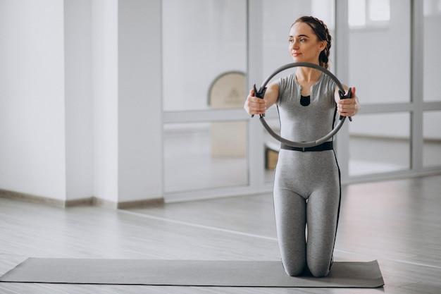 Donna che pratica yoga in palestra su una stuoia Foto Gratuite