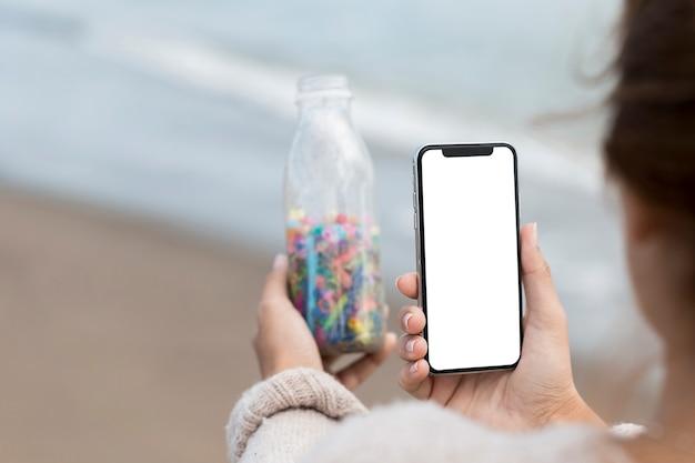 Donna che prende foto della bottiglia con plastica Foto Gratuite