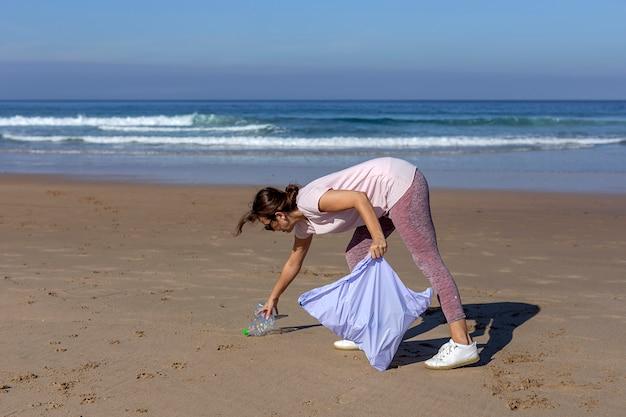 Donna che prende spazzatura e materie plastiche che puliscono la spiaggia Foto Premium