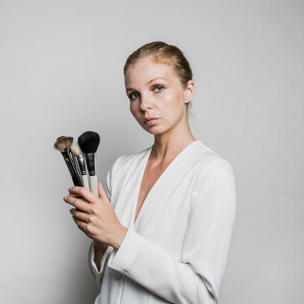 Donna che propone con le spazzole Foto Gratuite
