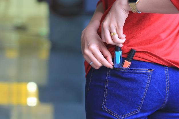 Donna che prova a rubare gli oggetti in un grande magazzino Foto Premium