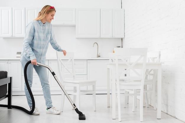Donna che pulisce casa con il vuoto Foto Gratuite