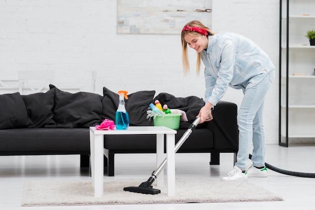 Donna che pulisce con l'aspirapolvere Foto Gratuite