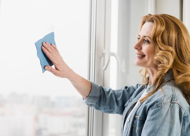 Donna che pulisce finestra con lo straccio Foto Gratuite