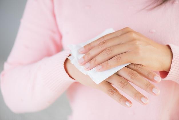 Donna che pulisce le sue mani con un fazzoletto. concetto di assistenza sanitaria. Foto Premium