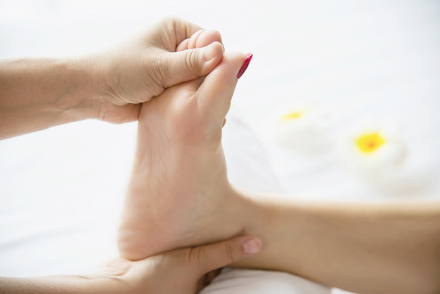 Donna che riceve il servizio di massaggio ai piedi da massaggiatrice vicino a portata di mano e piedi - rilassarsi nel concetto di servizio di massaggio di massaggio del piede Foto Gratuite
